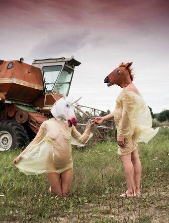 Nackter Mann mit Pferdemaske und Frau mit Einhornmaske auf dem Kopf in gelben Regenmänteln posiert auf dem Feld