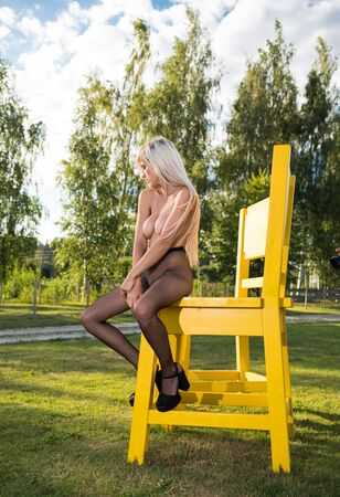 Beautiful blonde nude woman posing on a big chair in the garden. Sexy naked in black fishnet tights