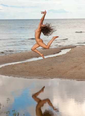 Young woman jumping at the beach. Sexy brunette posing outdoors