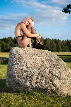 Young nude woman posingon the stone. Naked woman sunbathing and enjoying nature and summer time. Sexy blonde in black fishnet tights and in heels Banco de Imagens