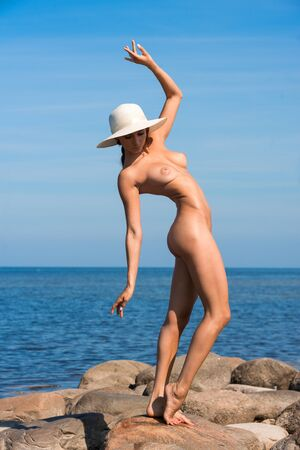 Young beautiful nude woman in a white hat posing at the beach. Enjoying summer time near the sea