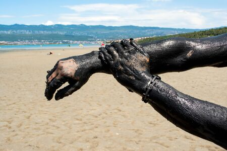 Man applying black healing clay. Relaxing at the spa resort