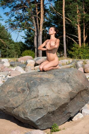 Yoga time. Young nude woman sitting on stone against nature background