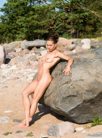 Young beautiful naked woman enjoying summer time at the beach. Sexy brunette posing near  big stone