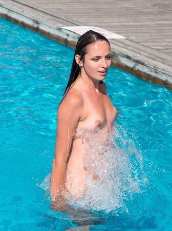 Beautiful young naked woman enjoying summertime in swimming pool