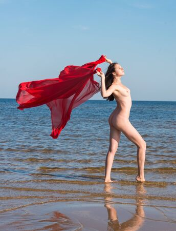 Beautiful woman with red fabric posing at sea beach