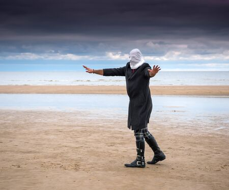 Man dressed in a black coat with closed head posing at the beach Stok Fotoğraf