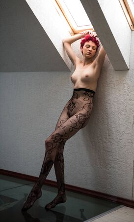 Gorgeous naked  posing indoors. Sexy nude woman posing near window Banco de Imagens