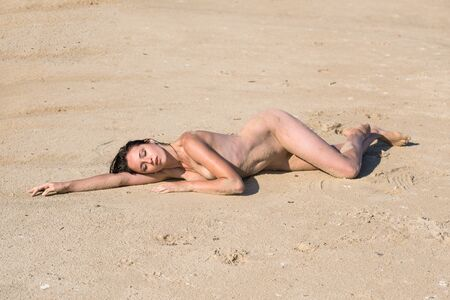 Young nude woman posing on a sandy beach. Sexy woman enjoying hot summer day outdoors