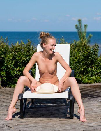 Beautifulsmiling  naked woman sunbathing on sunbed. Enjoying summer time Stockfoto