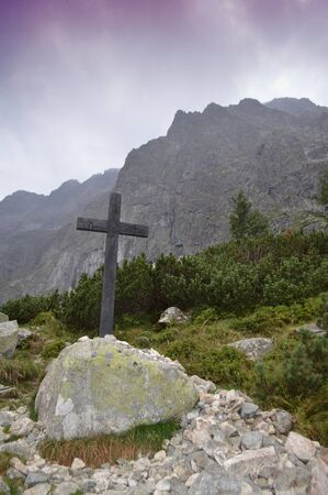 Christian cross on top of the hill of the mountains.  Religious concept