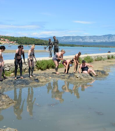 KRK, CROATIA -JULY 02, 2014:Healthy mud beach in Cizici Soline on Krk island, Kvarner bay of Croatia. Healing mud therapy helps with some skin diseases