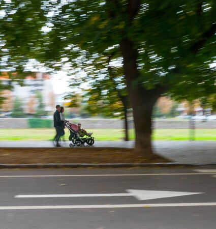 Family with small children in the strollers walking down the street. Intentional motion blur