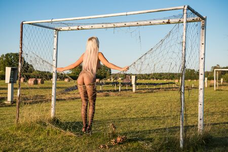 Nude woman in black fishnet tights and in heels posing near the football goal Stock Photo