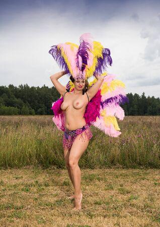 Jeune femme en costume de carnaval coloré lumineux posant à l'extérieur. Brune sexy se prépare pour le carnaval