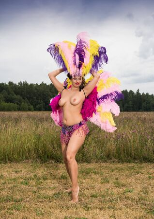Young woman in bright colorful carnival costume posing outdoors. Sexy brunette preparing for carnaval