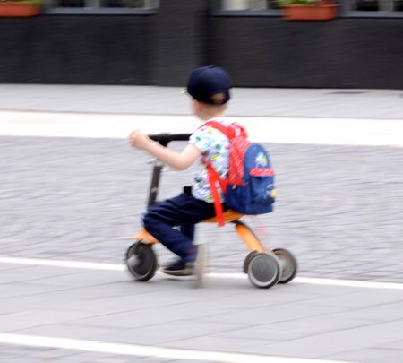 Small boy on tricycle in motion blur. Defocesed image