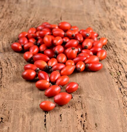 Rose hip (wild rose berries) on a wooden background