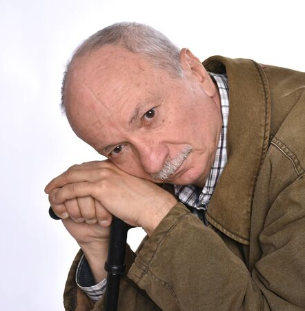 Sad lonely elderly man with a cane posing in studio on a white background Foto de archivo