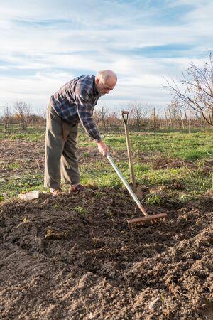 Granjero que trabaja con un rastrillo en el jardín en otoño