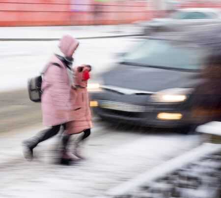 Dangerous situation on city roads on zebra crossing in winter time. Intentional motion blur
