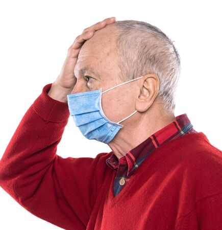 Portrait of sick old man in medical mask posing in studio on a white background