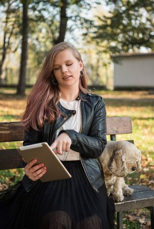 Cheerful female girl in casual wear using tablet in autumn sunny park. Happy teen girl outdoors