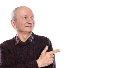 Smiling senior man pointing his finger to the side over white background