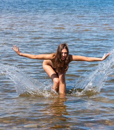 Beautiful young woman posing in the sea. Sexy brunette enjoying summertime at the beach