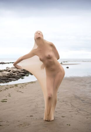 Nude model posing in stocking in the sea at the beach. Sexy woman outdoors Zdjęcie Seryjne