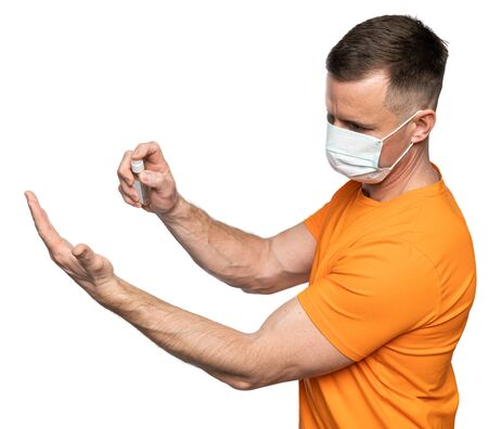 Healthcare and medical concept. Man in medical face mask and gloves handling hands with a disinfector over white background