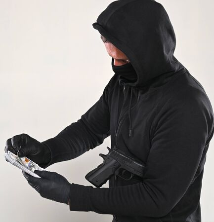 Man in black mask and hoody with a gun and pack of dollars over gray background