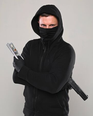 Man in black mask and hoody with a gun and pack of dollars over gray background Foto de archivo