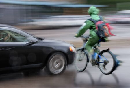 Dangerous city traffic situation with cyclist and car in the city in motion blur. Defocused image
