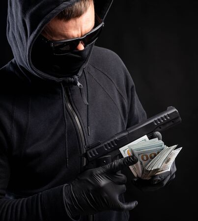 Man in black mask and hoody with a gun and pack of dollars over black background Stock Photo