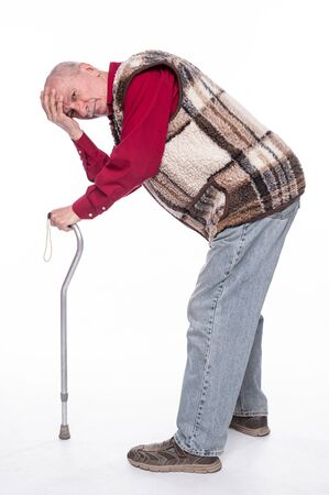 Healthcare concept. Unhappy senior man with a cane suffering from pain in back or reins over white background
