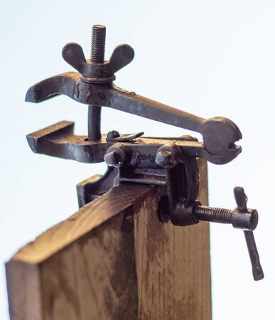 Old rusty vise for metal products over white background