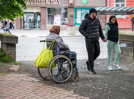 UZHHOROD, UKRAINE - MAY 04, 2020: Image of homeless beggar woman in wheelchair outdoors in Uzhhorod city, Ukraine Editorial