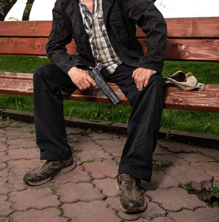 Man with a gun sitting on a bench outdoors