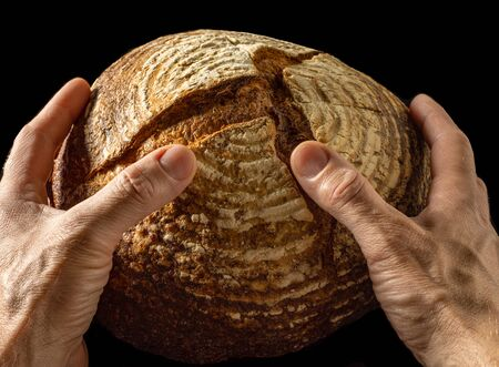 Freshly baked buckwheat bread in hands of a man