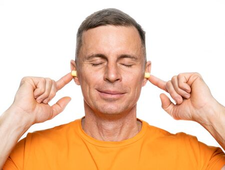 Young caucasian man inserting earplugs into his ears over white background Reklamní fotografie