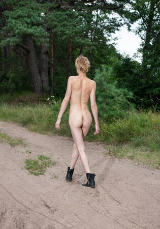Young nude woman walking in the forest. Sexy blonde outdoors 写真素材