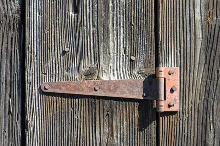Rusty hinge on an old wooden door, close up