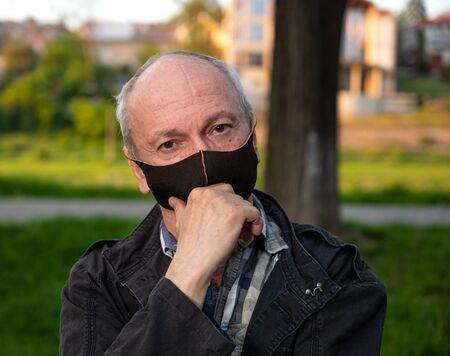 Senior man in facial mask outdoors in the park
