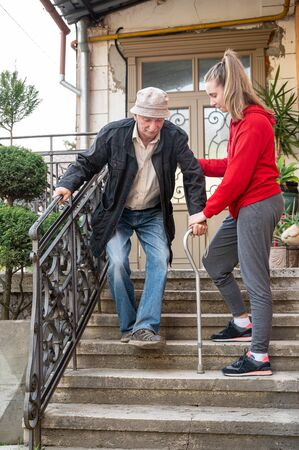 Senior man with walking stick walking with granddaughter outdoors