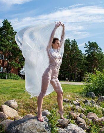 Young woman posing in polyethylene film on the beach Reklamní fotografie