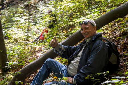 Holiday and leisure concept. Portrait of an elderly man resting and sitting in the forest Stock fotó - 149458565
