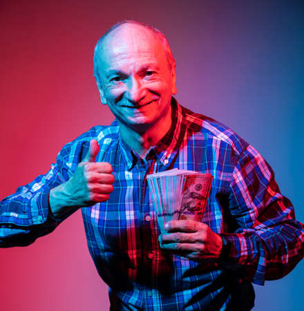 Smiling senior gentleman holding a stack of money and giving a thumb up in studio Reklamní fotografie