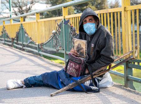 UZHHOROD, UKRAINE - APRIL 10, 2020: Homeless man begging for alms on a city street of Uzhhorod, Ukraine