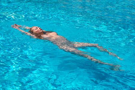 Beautiful young woman enjoying summertime in swimming pool